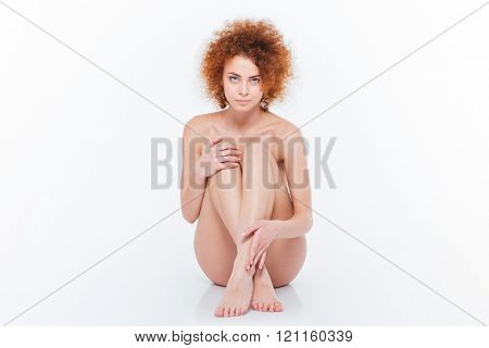 Beautiful nude woman sitting on the floor isolated on a white background