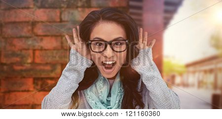 Asian woman shouting to the camera against view of brick wall