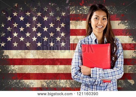 Smiling asian woman holding red book against usa flag in grunge effect