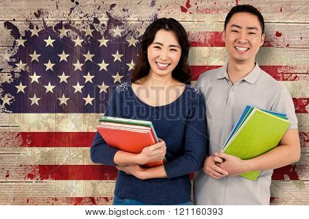 Happy couple holding books against usa flag in grunge effect