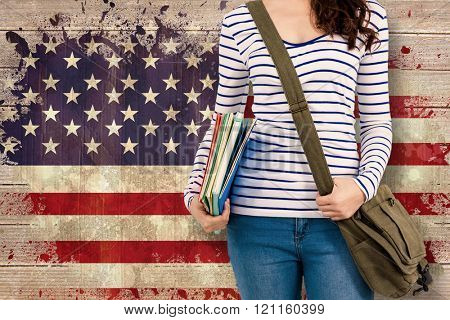 Mid section of man with should bag and files against usa flag in grunge effect