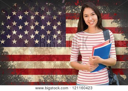 College girl holding books with blurred students in park against usa flag in grunge effect
