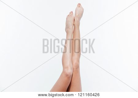 Closeup portrait of a sexy female legs raised up isolated on a white background