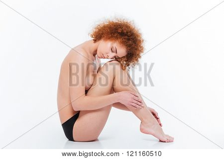 Sexy redhead woman with curly hair sitting on the floor isolated on a white background