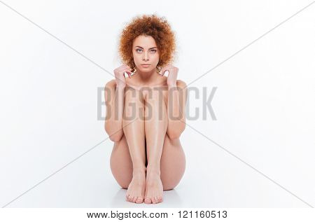 Naked redhead woman with curly hair sitting on the floor isolated on a white background