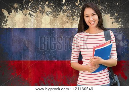 College girl holding books with blurred students in park against russia flag in grunge effect