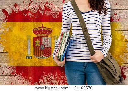 Mid section of man with should bag and files against spain flag in grunge effect