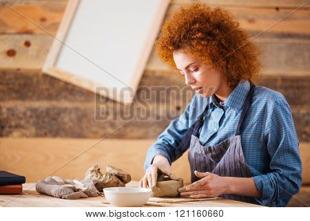 Creative young woman potter with curly red hair making earthen dishes in workshop