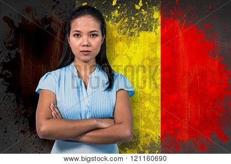 Serious businesswoman with arms crossed against belgium flag in grunge effect