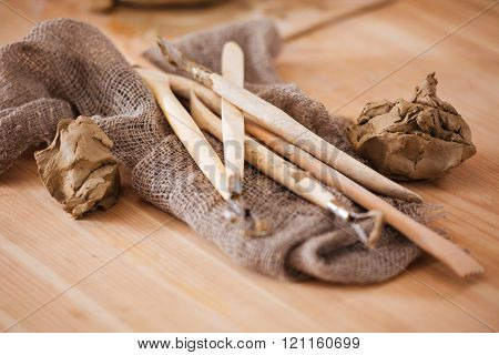Closeup of dirty professional tools of sculptor and pieces of clay on the table