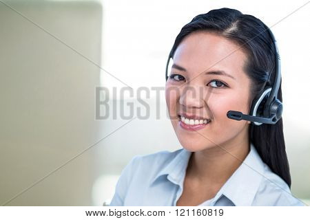 Smiling businesswoman using headset against steaming cup of coffee