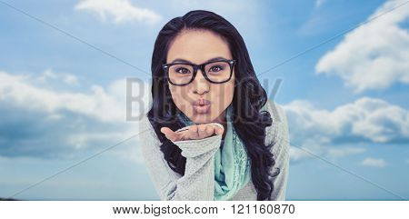 Asian woman blowing kiss to the camera against beach with blue sky