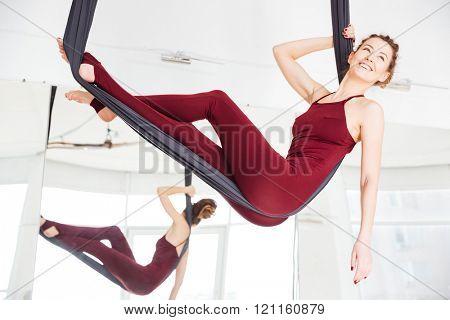 Happy attractive young woman relaxing in hammock in antigravity yoga studio