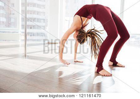 Beautiful young woman with dreadlocks bending and doing yoga in studio