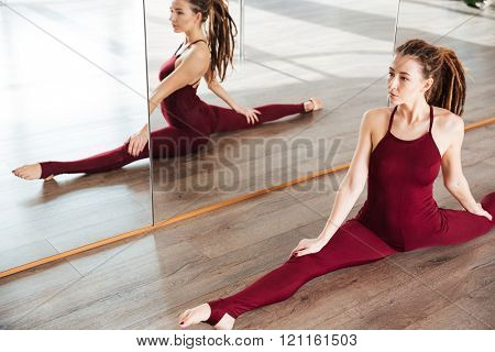 Charming young woman with dreadlocks doing twine on the floor near the mirror