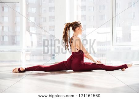 Profile of beautiful young woman with dreadlocks doing twin in dance studio
