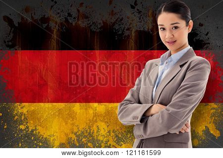 Portrait of a beautiful businesswoman posing with the arms crossed against germany flag in grunge effect