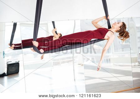 Focused beautiful young woman doing antigravity yoga in studio