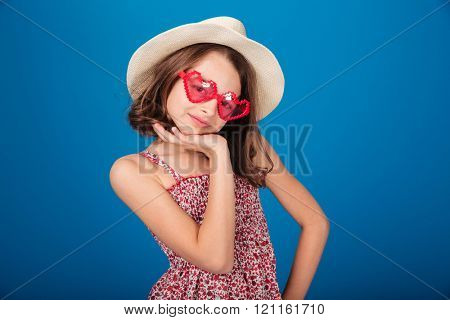 Cute smiling little girl in hat and heart shaped sunglasses standing and posing over blue background