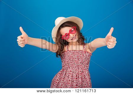 Cheerful pretty little girl in hat and heart shaped sunglasses  showing thumbs up over blue background