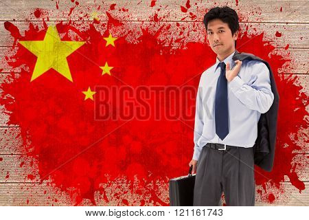 Portrait of a businessman holding a briefcase and his jacket on his shoulder against china