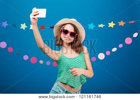 Cute playful little girl in hat and sunglasses taking selfie with mobile phone over blue background