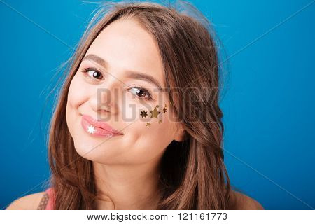 Beauty portrait of attractive smiling young woman with decoration on cheek over blue background