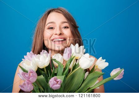 Cheerful beautiful young woman smiling and holding bouquet of spring flowers over blue background