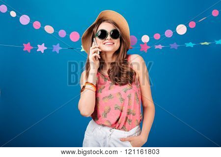 Cheerful attractive young woman in hat and sunglasses talking on mobile phone over blue background