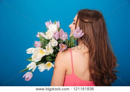 Back view of attractive smiling young woman with bouquet of flowers over blue background