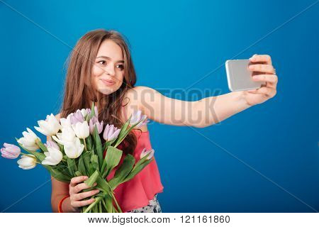 Pretty smiling young woman with bouquet of tulips taking selfie with mobile phone over blue background