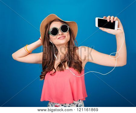 Smiling charming young woman listening to music from blank screen smartphone with earphones over blue background