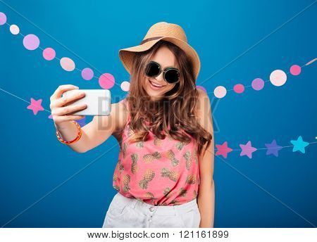 Smiling pretty young woman taking selfie using smartphone over blue background