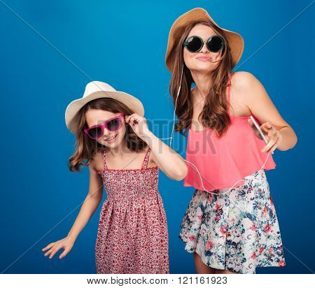Two cute happy sisters listening to music with earphones and dancing over blue background