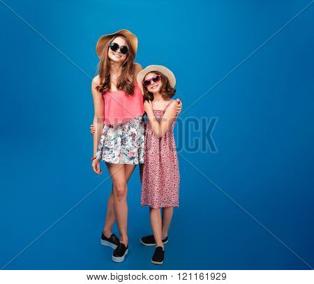 Two cheerful beautiful sisters standing together over blue background