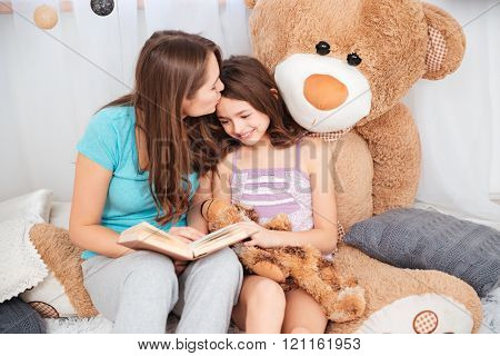 Two cute smiling sisters reading and kissing in children room
