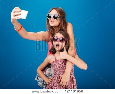 Two charming happy sisters in sunglasses taking selfie using smartphone over blue background