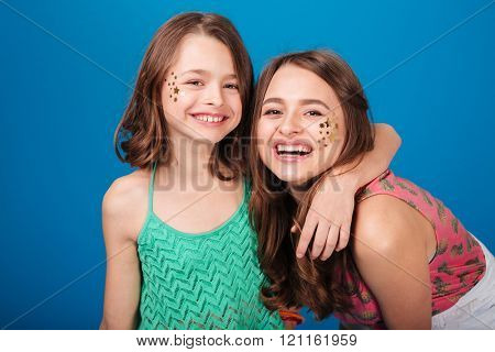 Portrait of two happy lovely sisters with decorations on cheeks laughing over blue background