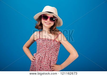 Pretty cheerful little girl in hat and glasses standing over blue background