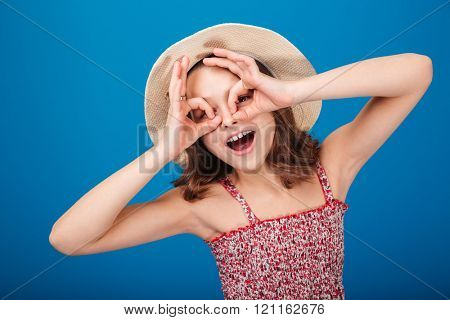 Funny playful little girl in hat making glasses by hands over blue background