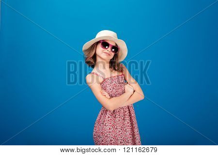 Lovely cheerful little girl in hat and sunglasses standing with arms crossed over blue backgound