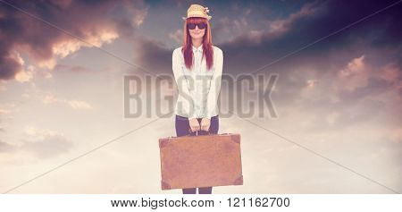 Portrait of a hipster woman holding suitcase against blue and orange sky with clouds