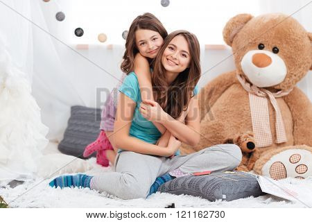 Portrait of two cheerful charming sisters sitting in children room at home