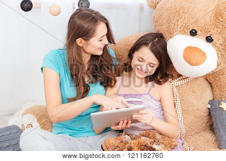Two cheerful cute sisters sitting and using tablet together at home