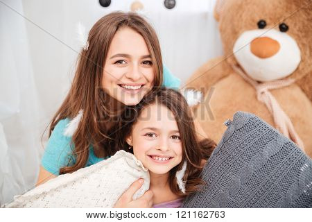 Two cheerful charming sisters playing with pillows at home