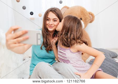 Two pretty smiling sisters kissing and making selfie in children room