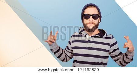 Hipster showing rock and roll hand sign against blue vignette background