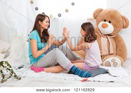 Two playful happy sisters sitting and playing together in children room at home