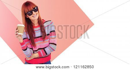 Attractive hipster woman holding a cup of coffee against red vignette