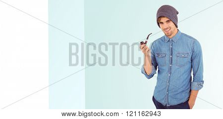 Portrait of hipster smiling while holding smoking pipe against blue background